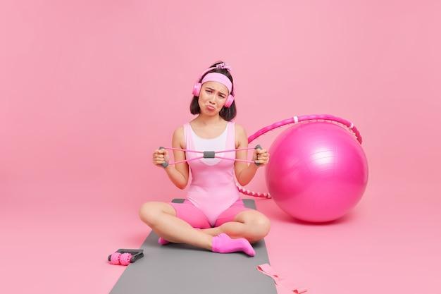 Женщина протягивает руки с лентой сопротивления, одетая в спортивную одежду, скрещивает ноги на коврике, слушает музыку через наушники в окружении спортивного оборудования. концепция здорового образа жизни