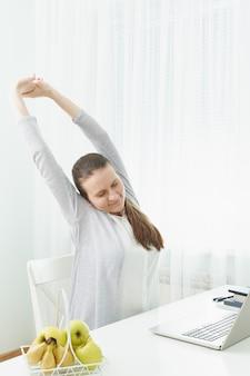女性は腕を伸ばし、疲労から背中をこねます。