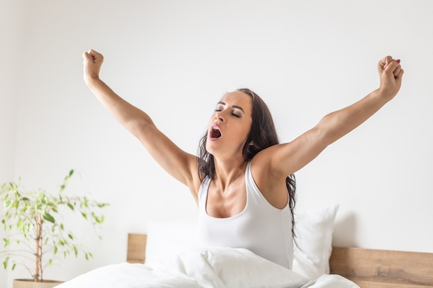 Woman stretches her arms wide open and yawns as she wakes up in the morning in the bed.