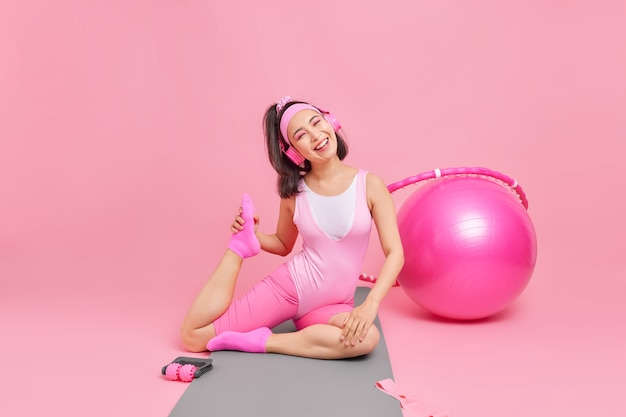 Woman stretches legs on fitness mat dressed in activewear tilts head listens music via headphones leads active lifestyle motivates you to do sport