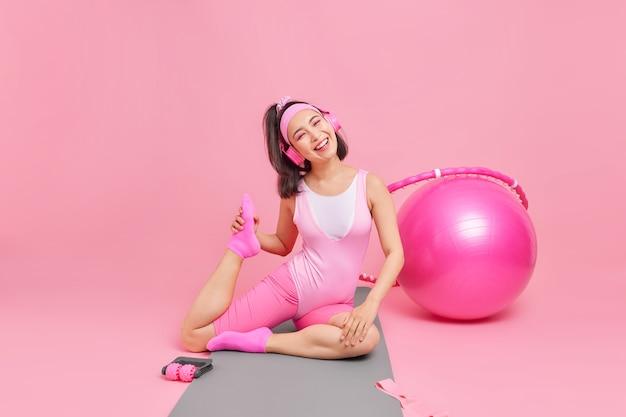 여자는 활동복을 입은 피트니스 매트에 다리를 뻗고 헤드폰을 통해 음악을 듣습니다. 활동적인 생활 방식이 스포츠를 하도록 동기를 부여합니다.