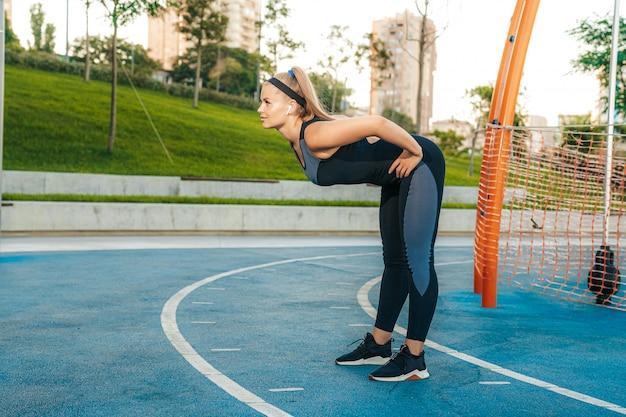 女性は屋外ジムで筋肉を伸ばす