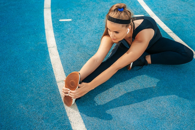 Женщина растягивает мышцы в тренажерном зале на открытом воздухе