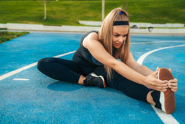 Woman stretches muscles in the outdoor gym