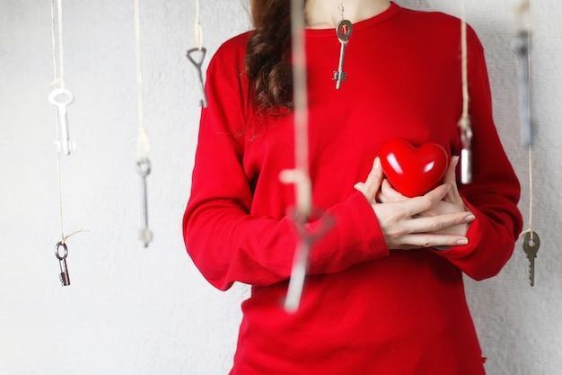 Женщина протягивает руку в форме красного сердца, окруженного ключевыми нитками