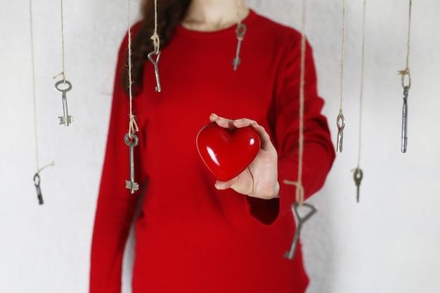여자는 열쇠 실로 둘러싸인 붉은 심장 모양으로 손을 뻗는다