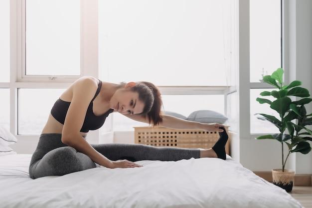 彼女のアパートの部屋でのトレーニングの後、ストレッチしてクールダウンする女性