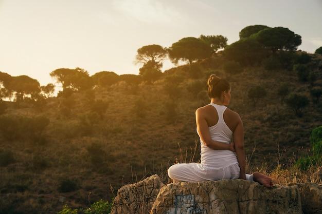 ストレッチと自然の中でリラックスしている女性