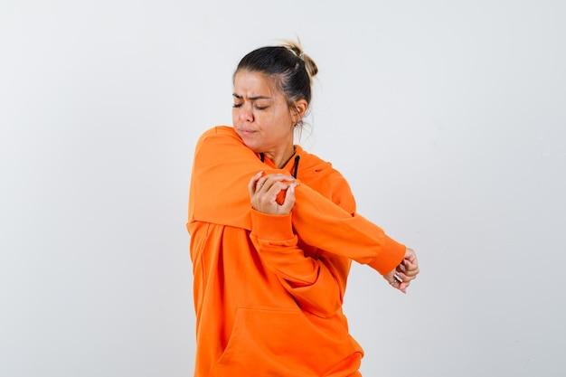 Donna che allunga il braccio con una felpa con cappuccio arancione e sembra pensierosa