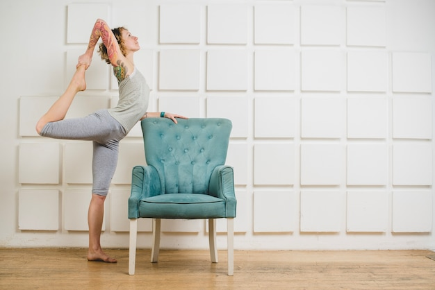 Woman stretching at armchair