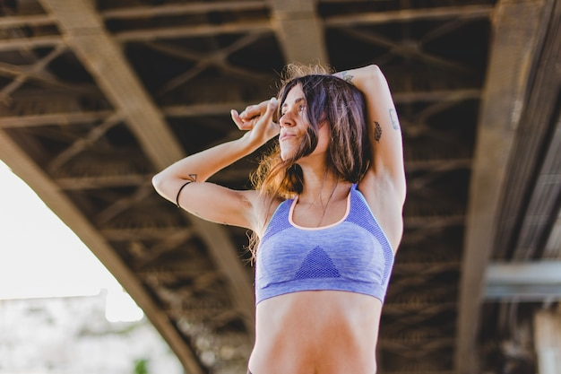 Woman stretching arms standing under bridge