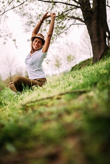 Woman stretching arms while sitting on grass in park.
