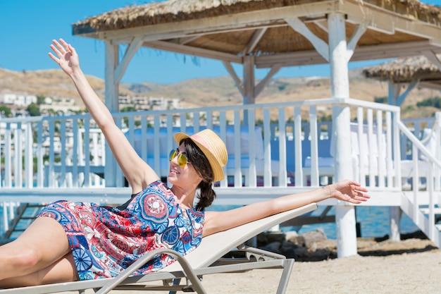 Donna che allunga le braccia mentre si è sdraiati su un'amaca