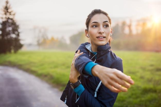 音楽を聴きながら公園でストレッチする女性。日没で運動している若い女性。公園で早朝にストレッチ運動をしている健康なスポーツの女の子。
