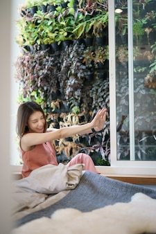 Woman stretching in bed after wake up in the morning, view from window on tropical garden.
