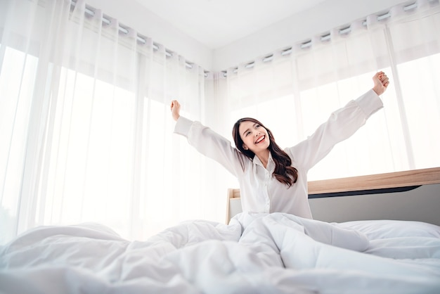 Woman stretching in bed after waking up.