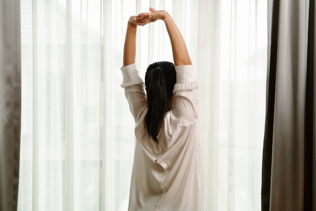 Woman stretching in bedroom after wake up, back view