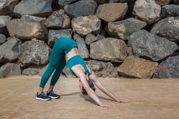 Woman stretching body in downward facing dog pose