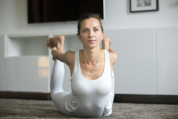 Woman stretching in bow exercise