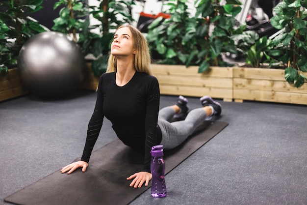 Woman stretching on exercising mat in gym