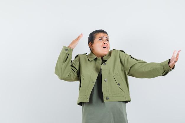 Женщина протягивает руку, пожимая плечами в куртке, футболке и выглядит взволнованной