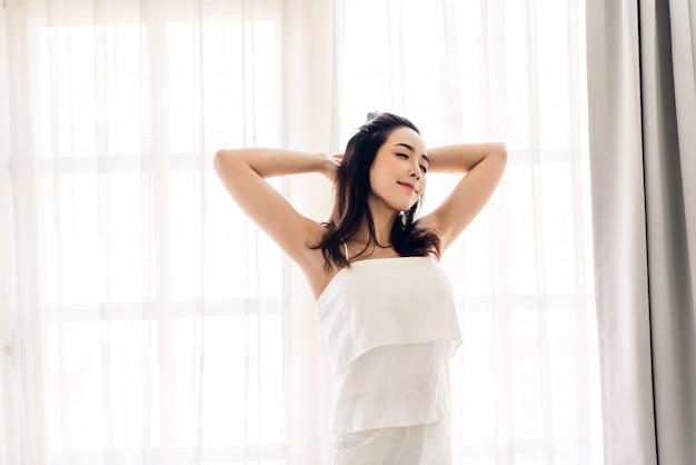 Женщина растягивается счастливой и расслабленной после того, как просыпается утром дома