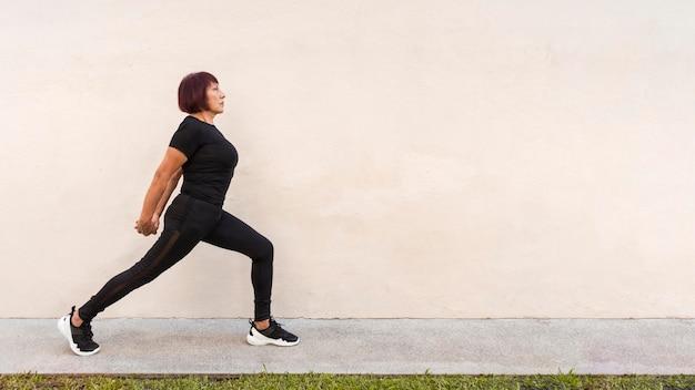 Женщина растягивает спину на открытом воздухе