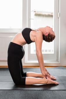 Женщина, растягивая спину спорт дома концепции