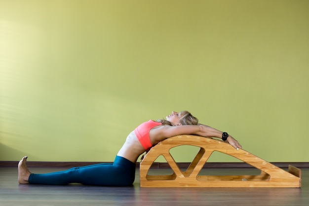 Woman stretching her back in a wooden contraption