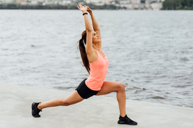 Woman stretching her body by a lake