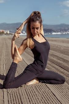 Женщина растягивает ноги во время занятий йогой на пляже
