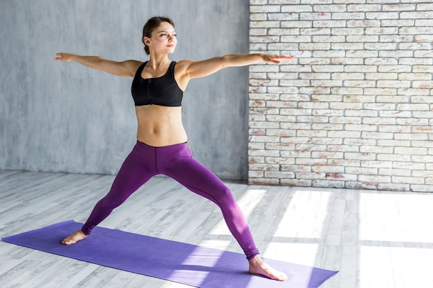 Woman stretching herself in a triangle yoga pose