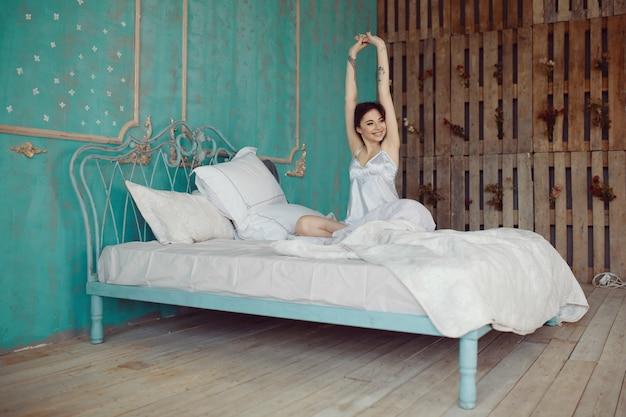目を覚ます後ベッドでストレッチの女性