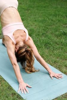 夏のクローズアップヨガの練習で公園でストレッチする女性