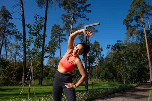 美しい緑豊かな公園で運動した後、体の左側を伸ばす女性
