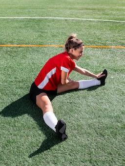 Donna che allunga la gamba sul campo