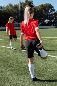 Donna che allunga la gamba sul campo di calcio a pieno tiro