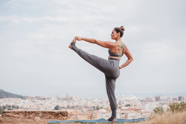 Woman stretching leg in front of city