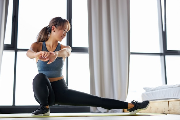 ヨガの前に足を伸ばしたり、マットの上でエクササイズをしたり、トレーニングをしたりする女性。健康的なライフスタイルとスポーツの概念