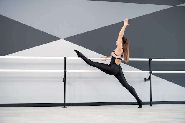 Woman stretching legs on handrails in dance studio