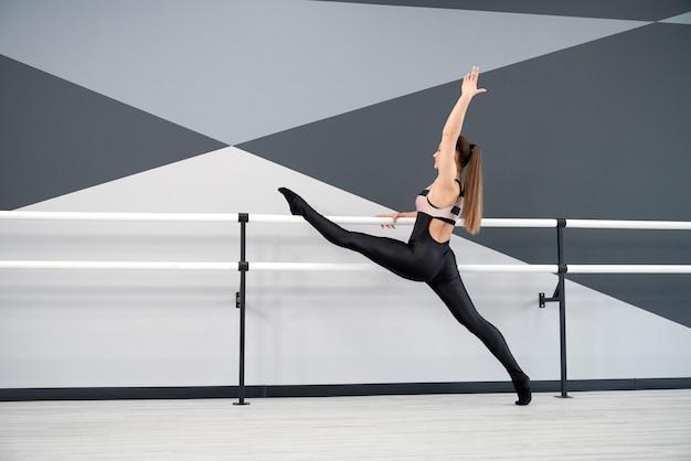 댄스 스튜디오에서 손잡이에 다리를 스트레칭하는 여자