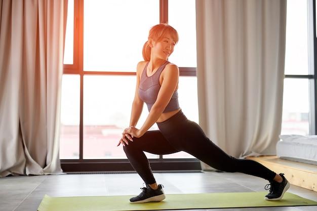 足を伸ばし、自宅でトレーニングする女性。フィットネス、トレーニング、瞑想、ヨガ、セルフケア、ピラティス、健康的なライフスタイルのコンセプト