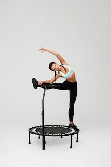 Woman stretching muscles staying on rebounder with leg on handle