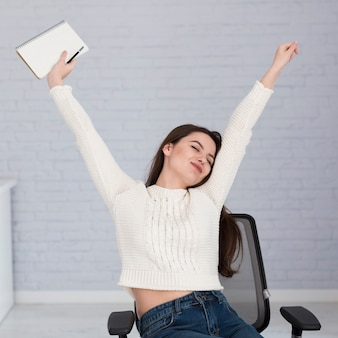 Woman stretching on chair in office