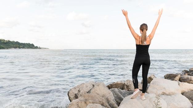 コピースペースでビーチでストレッチ女性