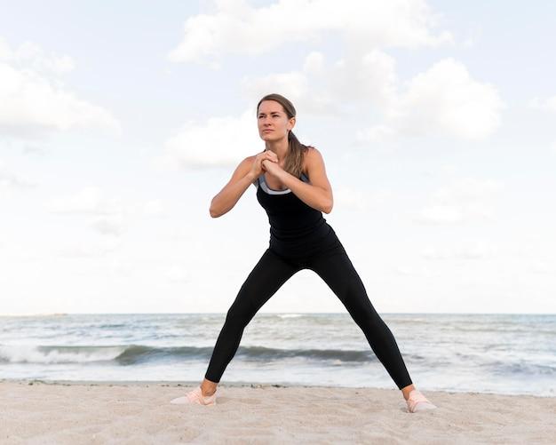 ビーチでストレッチする女性