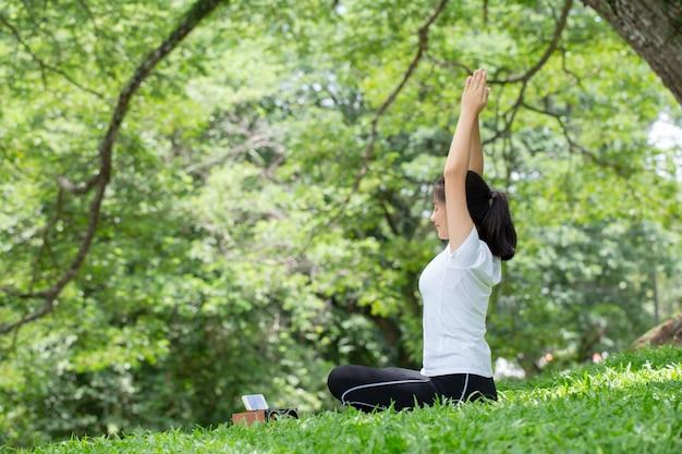 Женщина растягивается с позой йоги на природе. концепции здоровья.