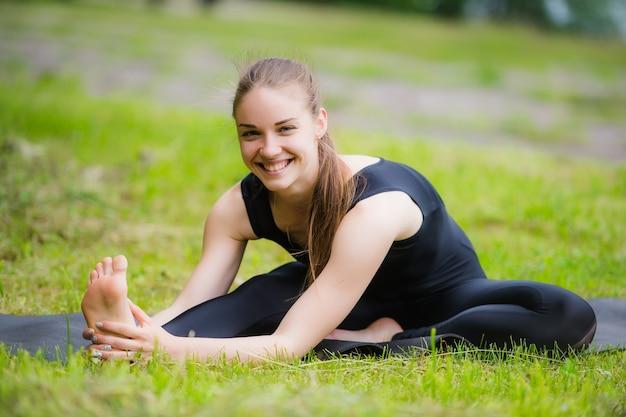 ヨガの練習の前に公園で屋外でストレッチする女性