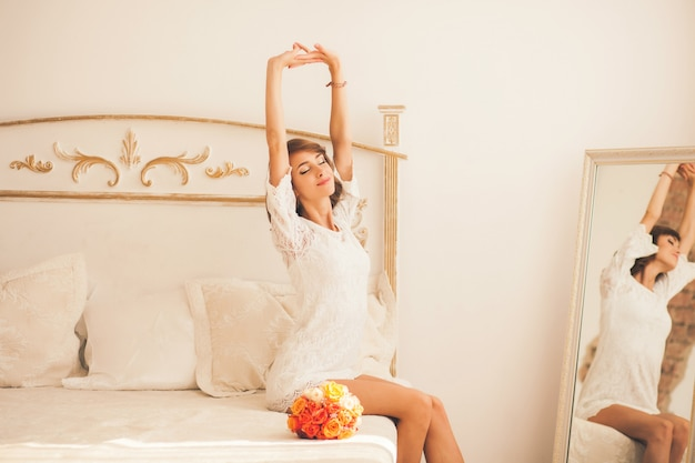 Woman stretching sitting on the bed