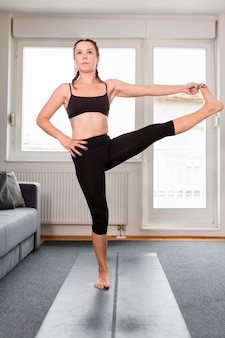 Woman stretching and standing on yoga mat